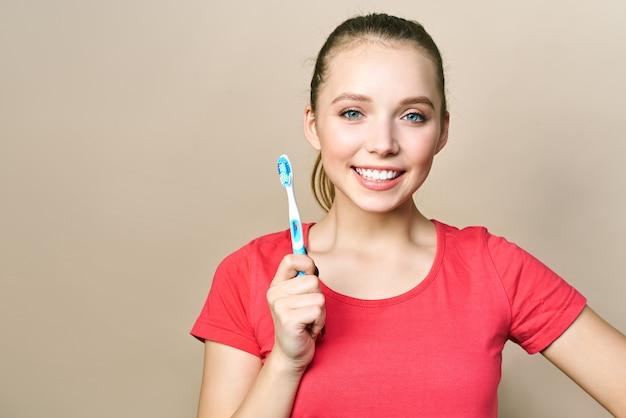 笑顔の若い女性は歯ブラシを保持しています。