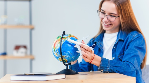 Young smiling woman holds in hand airplane model. happy beautiful girl planning vacation trip.