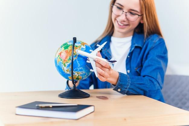 若い笑顔の女性は手に飛行機モデルを保持しています。休暇旅行を計画して幸せな美しい女の子。