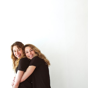 Young smiling woman hugging her sister from behind against white background