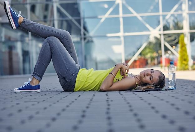 音楽を聴き、舗装に座ってtシャツを着た若い笑顔の女性