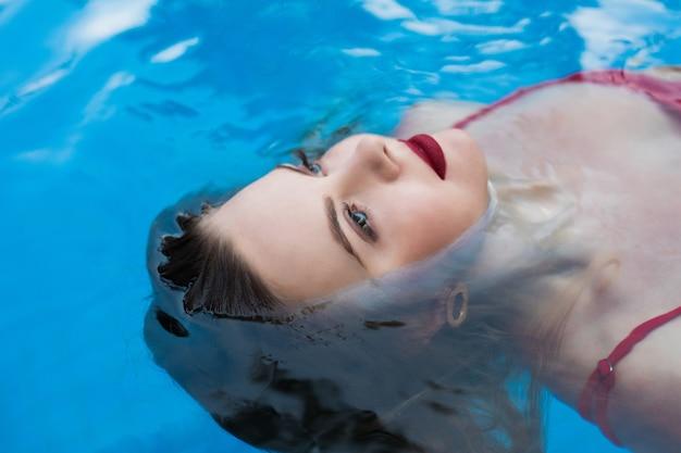 Молодая улыбающаяся женщина в бикини расслабляется, плавая на спине в чистой воде в бассейне. горячая красивая девушка в купальниках лежит в воде на солнышке на летних каникулах.