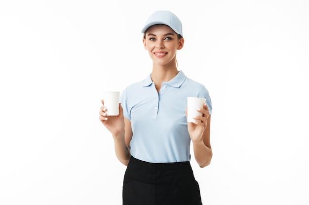 青いポロtシャツと帽子を手に幸せにしながら使い捨てカップを保持している若い笑顔の女性