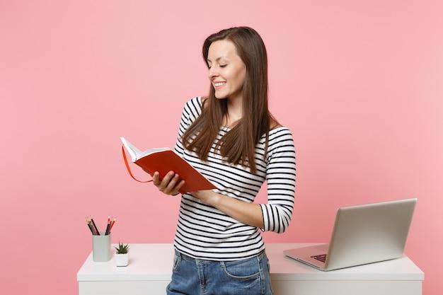 パステルピンクの背景に分離された現代的なpcラップトップと白い机の近くに立っているノートブックの仕事を保持しているカジュアルな服を着た若い笑顔の女性。業績ビジネスキャリアコンセプト。スペースをコピーします。