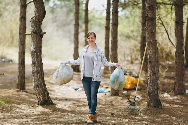 Молодая улыбающаяся женщина в повседневной одежде, держащая мешки для мусора, убирающая мусор в замусоренном парке или лесу. проблема загрязнения окружающей среды. остановить мусор природы, концепция защиты окружающей среды.