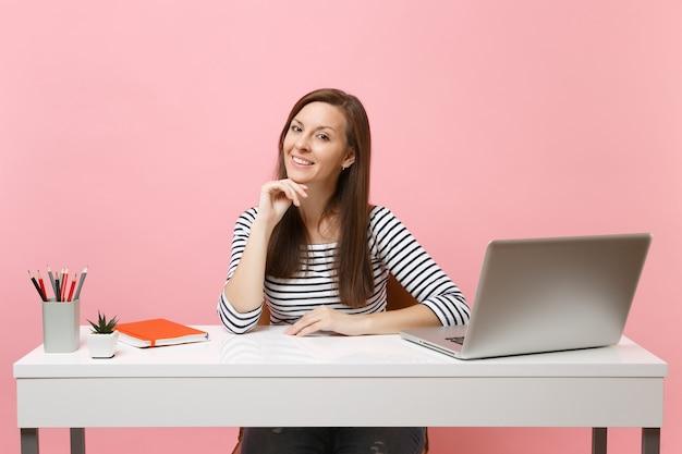 Молодая улыбающаяся женщина в повседневной одежде, опираясь подбородком на руку, сидит и работает за белым столом с современным портативным компьютером