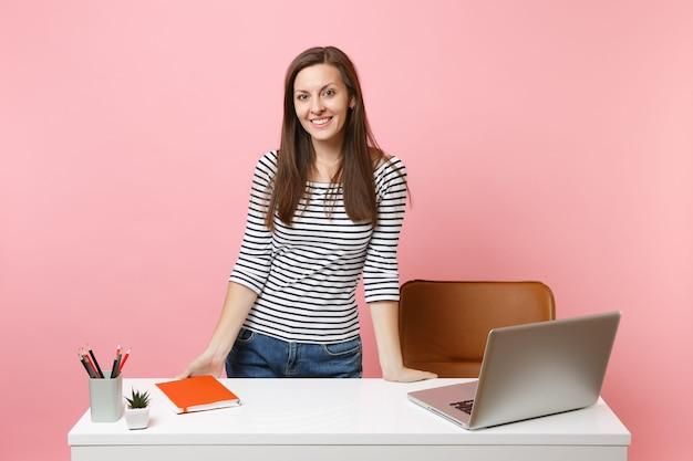 パステルピンクの背景に分離された現代的なpcのラップトップと白い机の近くに立って、カジュアルな服を着た若い笑顔の女性が働いています。業績ビジネスキャリアコンセプト。広告用のスペースをコピーします。