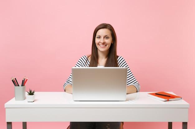사무실에 앉아 있는 동안 노트북으로 프로젝트 작업을 하는 캐주얼 옷을 입은 젊은 웃는 여성