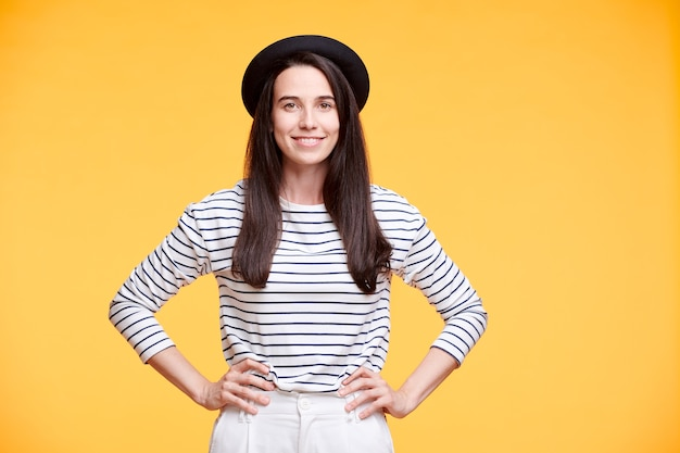 分離で黄色の壁でポーズをしながら彼女の腰に手を保つカジュアルウエアで若い笑顔の女性
