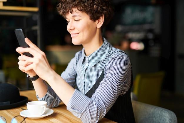 スマートフォンでスクロールまたはカフェでお茶をしながらビデオを見てカジュアルウェアの若い笑顔の女性