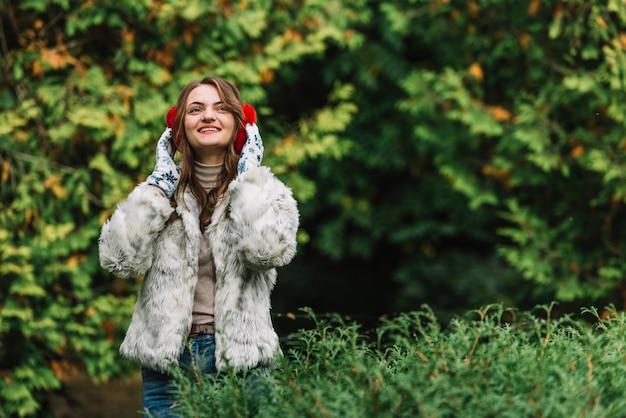 Молодая женщина улыбается в наушники в парке