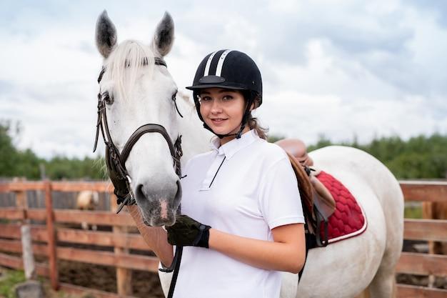 Молодая улыбающаяся женщина в конной экипировке смотрит на вас, стоя рядом с белой скаковой лошадью перед камерой