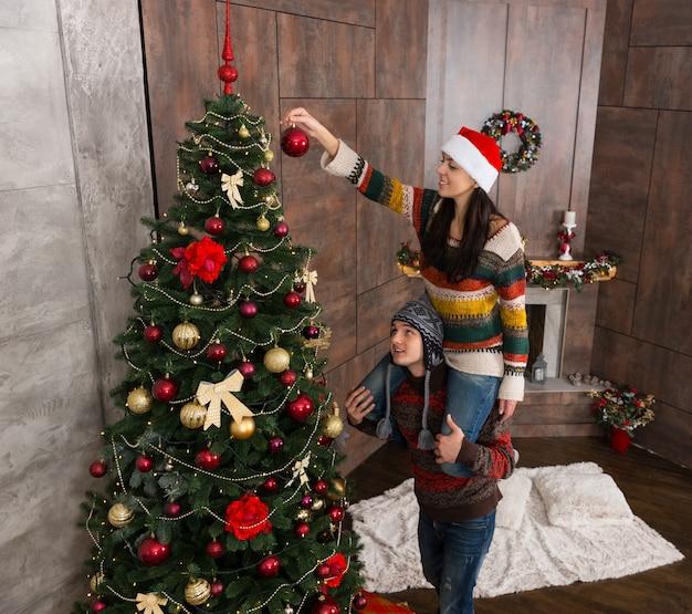 彼女のボーイフレンドの首に座って、装飾された暖炉のあるリビングルームの大きなクリスマスツリーに装飾を掛ける面白い帽子をかぶった若い笑顔の女性