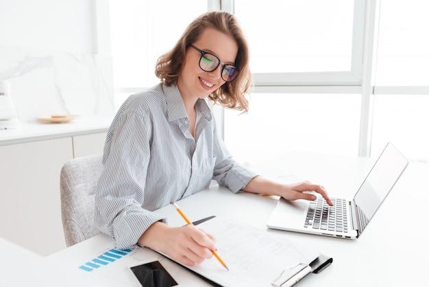 メガネとストライプのシャツの若い笑顔の女性がライトキッチンのテーブルに座りながらドキュメントとコンピューターを操作