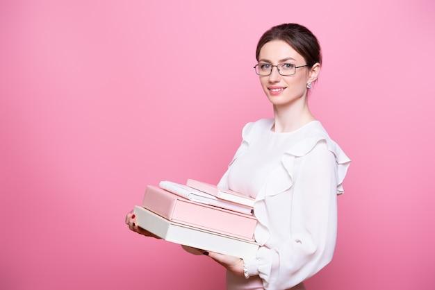 眼鏡をかけた若い笑顔の女性は、フォルダーを保持します。
