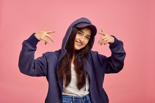 Молодая женщина улыбается в толстовке с капюшоном, розовая стена, эмоции. выражение лица, лицо женского пола, смотрящее на камеру в студии, эмоциональная концепция, чувства