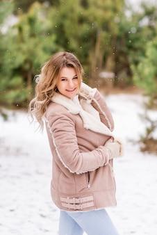 冬の森のピンクの服を着た若い笑顔の女性