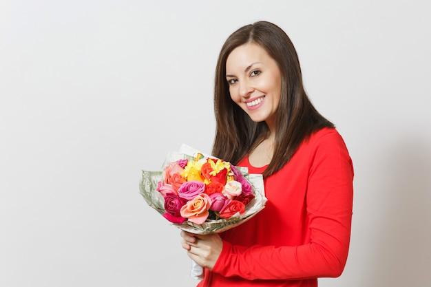 흰색 배경에 격리된 아름다운 장미 꽃다발을 들고 빨간 옷을 입은 젊은 웃는 여자. 광고 공간을 복사합니다. 성 발렌타인 데이 또는 국제 여성의 날 개념.
