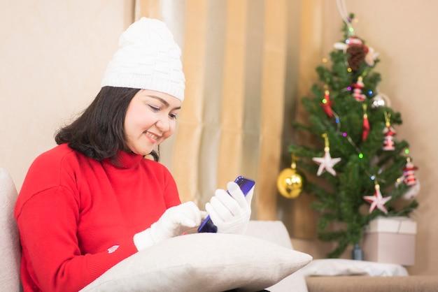 Молодая улыбающаяся женщина в красном свитере с помощью смартфона на диване в гостиной в зимний сезон