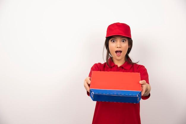 상자에 피자를 제공하는 빨간 제복을 입은 젊은 웃는 여자.