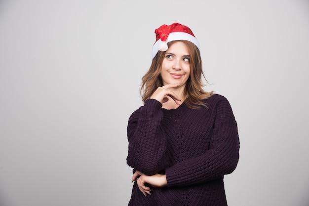 Молодая улыбается женщина в шляпе санта клауса стоя и позирует.