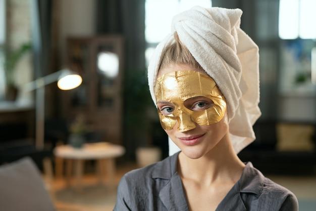シルクグレーのパジャマ、頭にタオル、顔に金色の化粧マスクで若い笑顔の女性が自宅のベッドでリラックスしてあなたを見ています