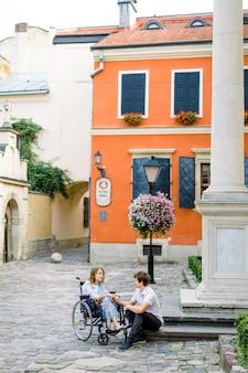 車椅子と石の階段に座っているハンサムな男の若い笑顔の女性