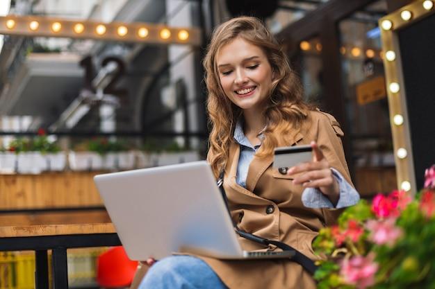 Молодая улыбающаяся женщина в плаще, держащая в руке кредитную карту, счастливо работает на ноутбуке, проводя время на улице на уютной террасе кафе