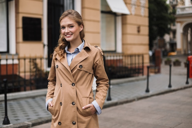 Молодая улыбающаяся женщина в плаще радостно