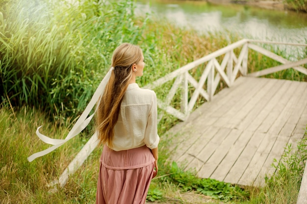 호수 목재 부두에 빈티지 복고 스타일 옷을 입고 젊은 웃는 여자
