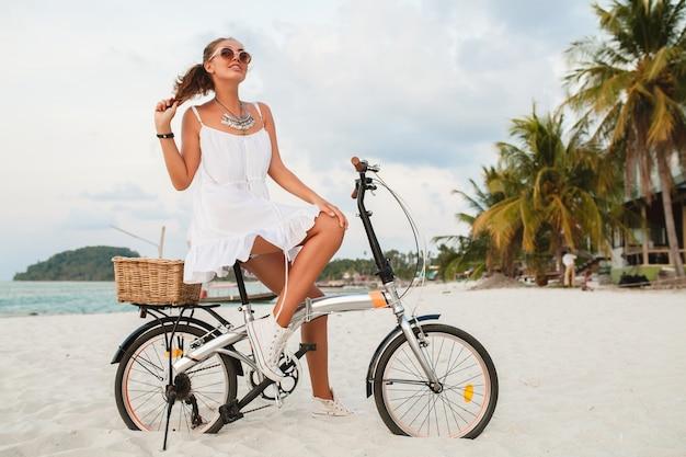 태국에서 여름 휴가를 여행하는 자전거 선글라스에 열대 해변을 타고 흰 드레스에 젊은 웃는 여자