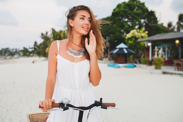 태국에서 여름 휴가를 여행하는 자전거와 함께 열 대 해변에서 산책하는 흰 드레스에 젊은 웃는 여자