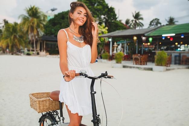 タイの夏休みに自転車で熱帯のビーチを歩く白いドレスを着た若い笑顔の女性