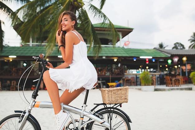 Молодая улыбающаяся женщина в белом платье гуляет на тропическом пляже с велосипедом, путешествуя на летних каникулах в таиланде Бесплатные Фотографии