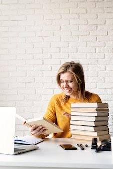 Молодая улыбающаяся женщина в желтом свитере читает книгу и смеется