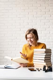 Молодая улыбающаяся женщина в желтом свитере учится на ноутбуке и читает книгу