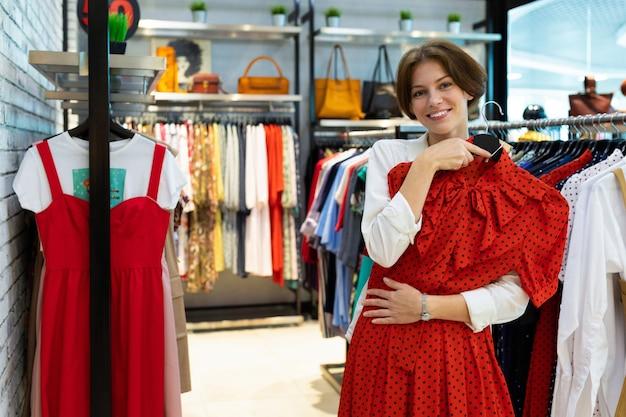 Молодая усмехаясь женщина держит платье полька-точки в магазине одежды