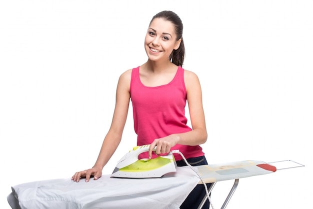 Young smiling woman is ironing a shirt with a steam iron.
