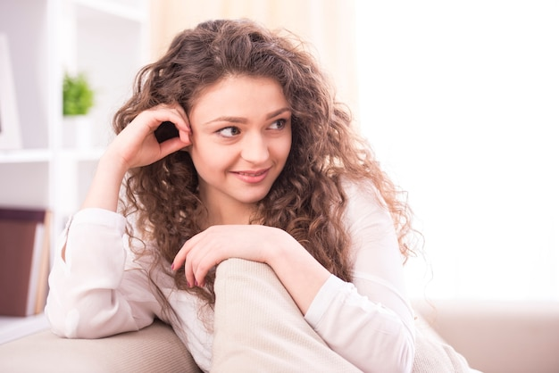 Young smiling woman is sitting on a couch at home.