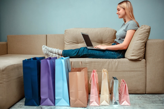 若い笑顔の女性はソファーに座っているとカラフルなショッピングバッグの近くのラップトップを使用して