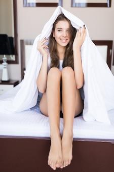 Giovane donna sorridente è seduta con una coperta sopra la testa a letto con lenzuola bianche, concerto in hotel, appartamento moderno