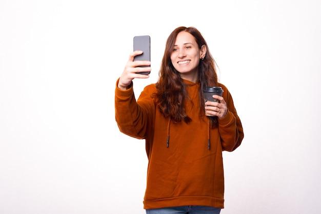 若い笑顔の女性は白い壁の近くで彼女の手にコーヒーを持って写真を撮っています