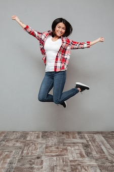 회색 벽 위로 점프 젊은 웃는 여자.