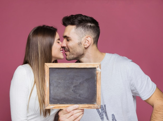 Young smiling woman kissing with positive man and showing photo frame