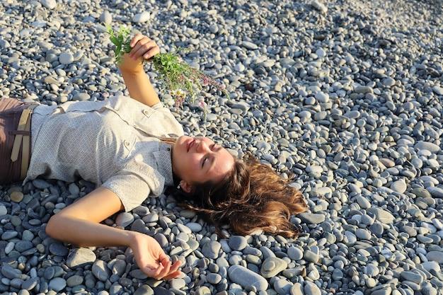 Молодая улыбающаяся женщина, лежащая на гальке и держащая небольшой букет полевых цветов