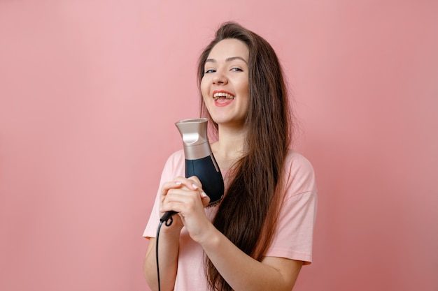 Young smiling woman like gangster with hairdryer in hands on pink background