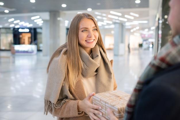ギフトボックスを取って、モール環境で彼に感謝を与えている間彼女の夫を見て若い笑顔の女性