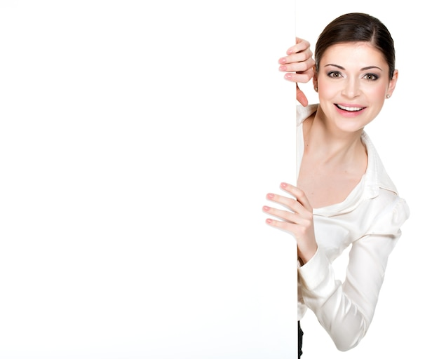 Young smiling woman looking from white blank banner - on white space