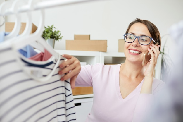 Young smiling woman looking at striped pullover on hanger