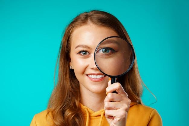 虫眼鏡を通して見ている若い笑顔の女性